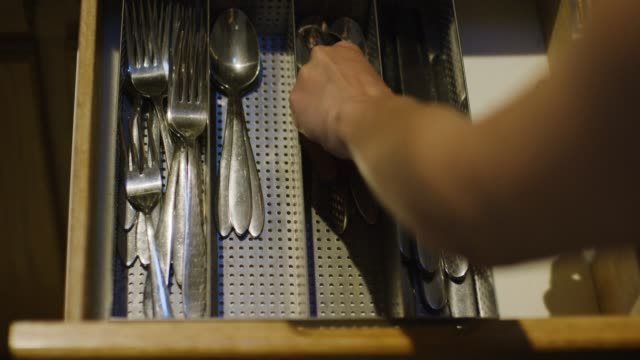 a caucasian woman's hands open a kitchen drawer, remove a cutlery place setting (a fork, a spoon, and a table knife) from a silverware organizer, and close the drawer - putting stock videos & royalty-free footage