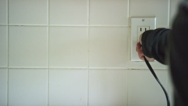 a caucasian woman's hands plug an electrical cord into a vertical american electrical outlet then unplugs the cord - electrical plug stock videos & royalty-free footage