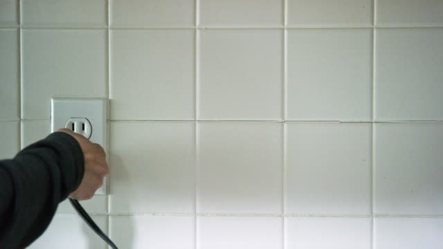 a caucasian woman's hands plug an electrical cord into a vertical american electrical outlet then unplugs the cord - power cable stock videos & royalty-free footage