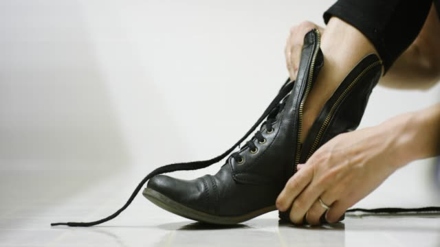 a caucasian woman's hands put on a black boot, zip it up, and tie the laces on the floor of a white bathroom - boot stock videos & royalty-free footage