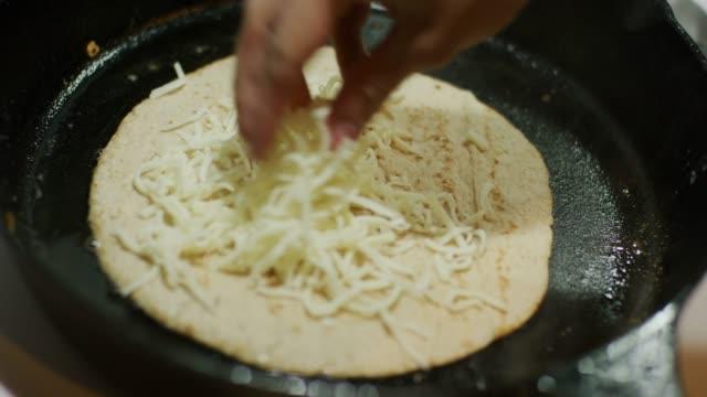 白人の女性の手は、鋳鉄でケサディーヤを調理しながら、トルティーヤにすりおろしたモッツァレラチーズをふりかけ、レンジバーナー - cheese点の映像素材/bロール
