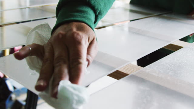 A Caucasian Woman's Hands Use a Paper Towel to Clean Several Pieces of Plexiglass