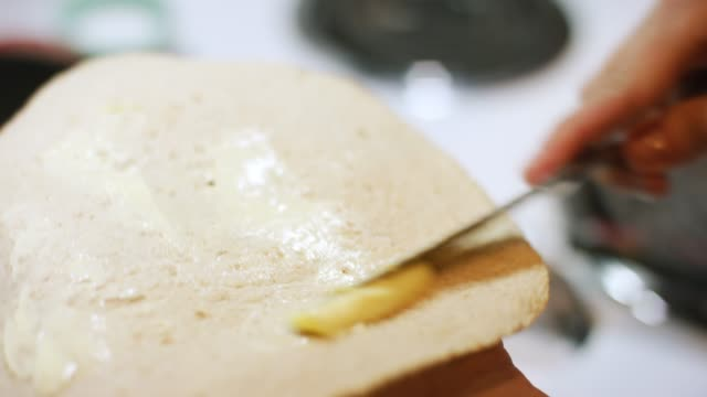 vídeos y material grabado en eventos de stock de las manos de una mujer caucásica usan un cuchillo de mesa para esparcir la mantequilla sobre una tortilla antes de colocarla en una quesadilla en una sartén de hierro fundido en un quemador de rango - sartén