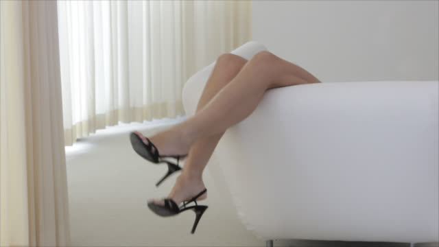 "vídeos y material grabado en eventos de stock de ""caucasian woman's legs on sofa, kicking off shoes"" - calzado"