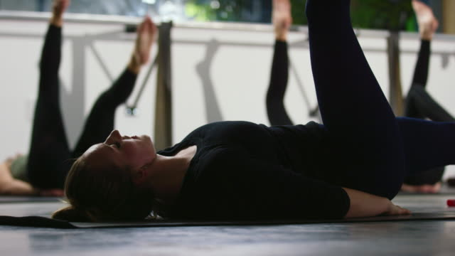 A Caucasian Women in Her Twenties Leads Her Exercise Class in Laying Down Pilates Leg Extensions in a Gym