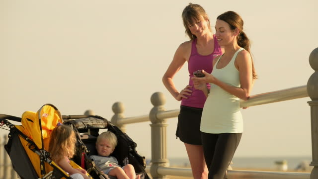 Caucasian women joggers resting with children in strollers