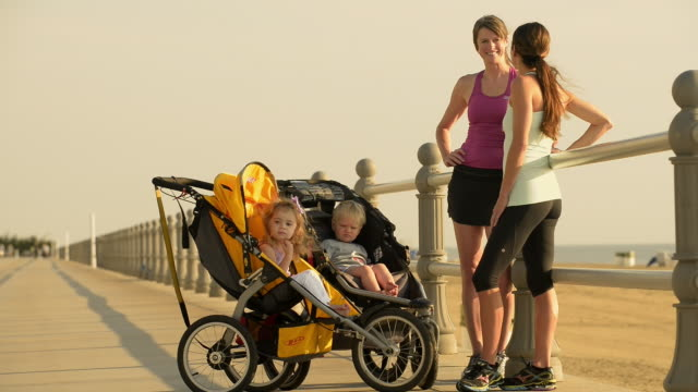 caucasian women joggers resting with children in strollers - pushchair stock videos and b-roll footage