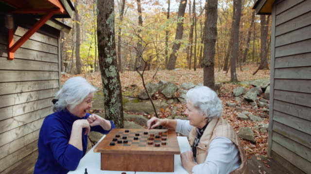 caucasian women playing checkers outdoors in autumn - draughts stock videos & royalty-free footage