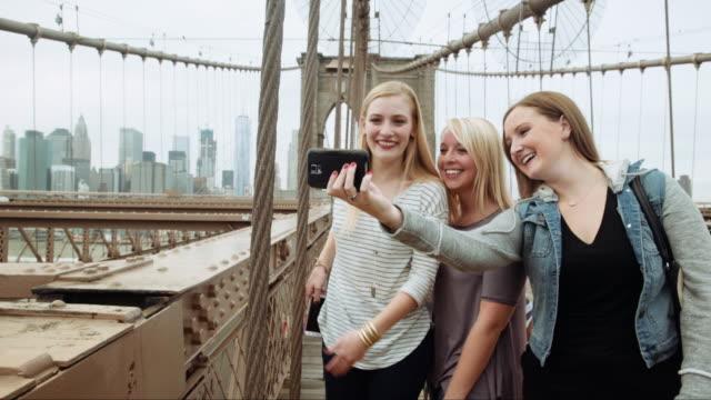 Caucasian women posing for cell phone selfies on bridge
