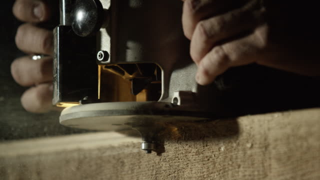 a caucasian woodworker uses a router along the edge of a red oak board as sawdust sprays into the air - wood material stock videos & royalty-free footage