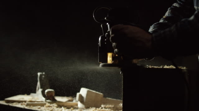 A Caucasian Woodworker Uses a Router Along the Edge of a Red Oak Board as Sawdust Sprays on to a Work Table, a No.5 Plane, and a Homemade Wooden Mallet All Against a Black Background