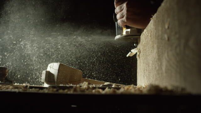 a caucasian woodworker uses a router along the edge of a red oak board as sawdust sprays on to a work table and a homemade wooden mallet - diy stock videos & royalty-free footage