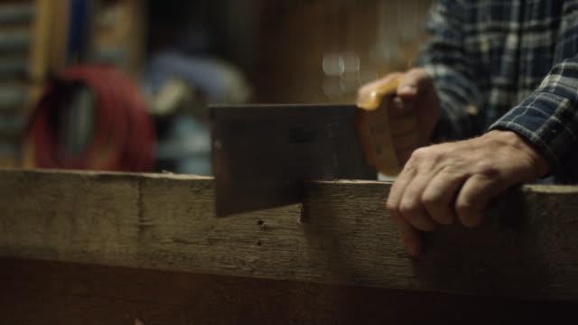 vídeos y material grabado en eventos de stock de un carpintero caucásico utiliza una mano antigua sierra a sierra una tabla de roble rojo en un taller - madera material de construcción