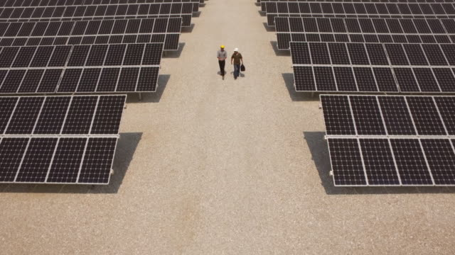 Caucasian workers walking near solar panels
