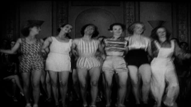 caucasian young adult female dancers at rehearsal; adult caucasian male choreographer demonstrates routine. dancers kick up legs. chorus girls hands... - 1930 video stock e b–roll