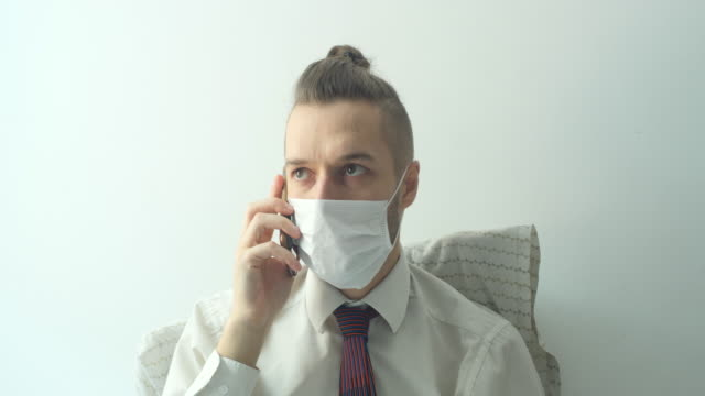 caucasian young blond hair man wears a white shirt with a tie and a disposable face mask for cough, flu, virus, viral protection. he stays home and calls on his phone in bed because of the quarantine - shirt and tie stock videos & royalty-free footage