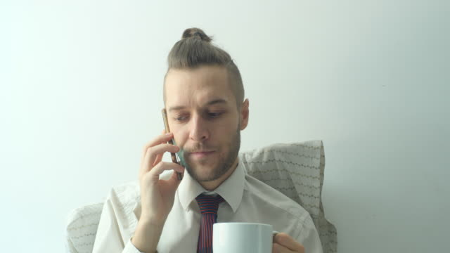 a caucasian young blond hair man wears a white shirt with a tie, stays home, calls on his phone and drinks coffee in a white cup in the bed in quarantine - shirt and tie stock videos & royalty-free footage