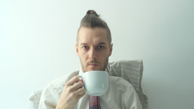 a caucasian young blond hair man wears a white shirt with a tie, stays home and drinks coffee in a white cup in the bed in quarantine - shirt and tie stock videos & royalty-free footage