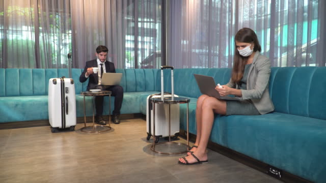 caucasian young businesswoman wearing formal clothes and protective covering mask sitting, wiping the surface of the laptop by ethanol spray and disposable paper to protect life and safety from covid-19 pandemic while waiting in the lobby of the hotel. - luggage stock videos & royalty-free footage