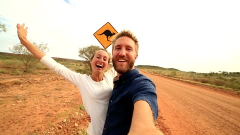 caucasian young couple take selfie portrait with kangaroo crossing sign - road warning sign stock videos & royalty-free footage
