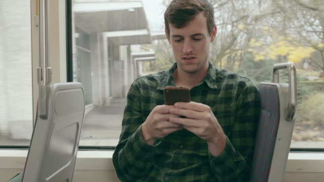 caucasian young male adult texting while riding the streetcar - bus stop stock videos & royalty-free footage