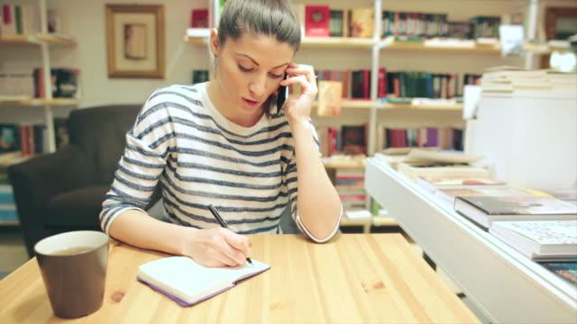 Caucasico giovane donna parlando al telefono e scrivere appunti.