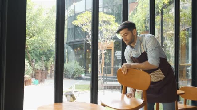 caucasion cameriere maschio tiene le sedie prima dell'apertura della caffetteria. imprenditore che apre una piccola caffetteria. - cumulo video stock e b–roll