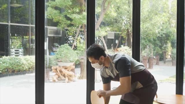 caucasion uomo bianco allevare sedie per allevare una caffetteria e pulire. - cumulo video stock e b–roll