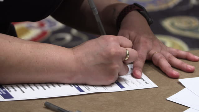 caucus goer fills out information on a presidential preference card as 2020 nevada caucus goers gathered at the grand ballroom at the bellagio to... - voting stock videos & royalty-free footage