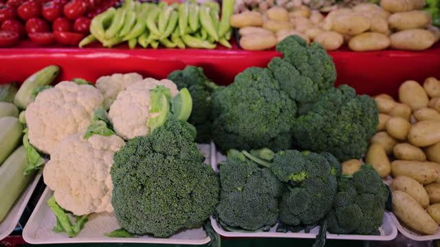 blumenkohl und brokkoli auf dem markt - marktstand stock-videos und b-roll-filmmaterial