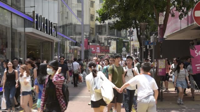 causeway bay, hong kong, china, monday, aug. 10, 2015. shots: wide shot, shoppers and pedestrians walk past a forever 21 inc. clothing store, right,... - times square causeway bay stock videos & royalty-free footage