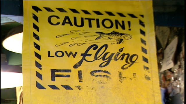 cu caution flying fish sign at pike place fish market seattle washington - pike place market stock videos and b-roll footage
