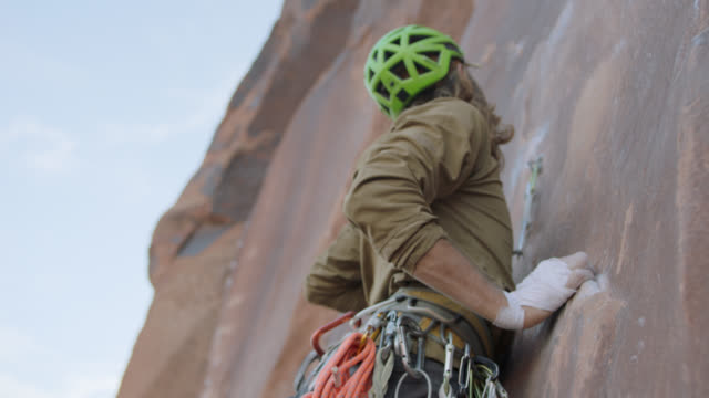 SLO MO. Cautious rock climber looks down and takes deep breaths as he climbs steep sandstone rock face.