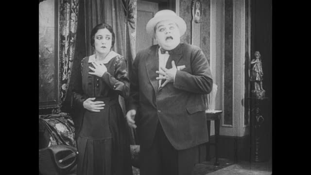1917 cautious woman approaches thief's front door and a flustered man (fatty arbuckle) hides in the pantry - fatty arbuckle stock videos and b-roll footage