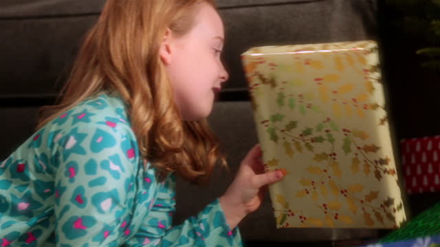 Cautious young girl looks over her shoulder before shaking presents beneath Christmas tree