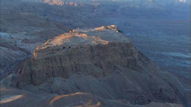ws aerial pov cave on mountain / masada, sourn judea desert, israel  - 聖地パレスチナ点の映像素材/bロール