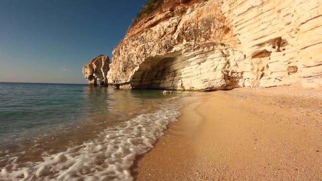 vídeos de stock, filmes e b-roll de cave on the beach with small waves - grotto cave