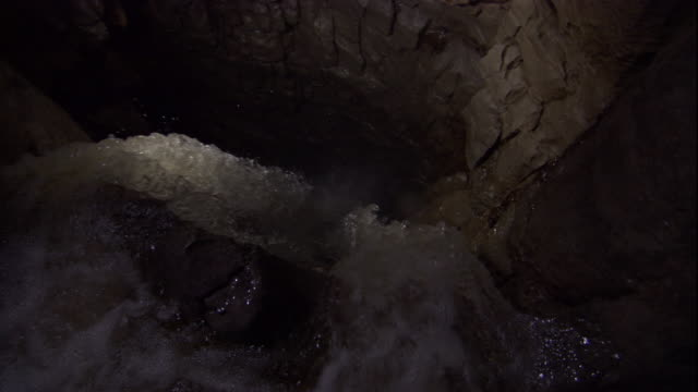 a cave waterfall pours over a cliff and into a deep pool. available in hd. - river stock videos & royalty-free footage