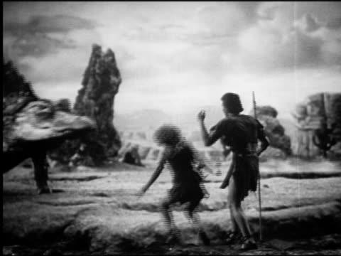 vídeos de stock, filmes e b-roll de b/w caveman + cavewoman jumping into ditch to hide from approaching dinosaur (lizard) - monstro