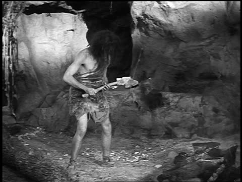 B/W caveman holding tool picking up circular piece of rock to make wheel