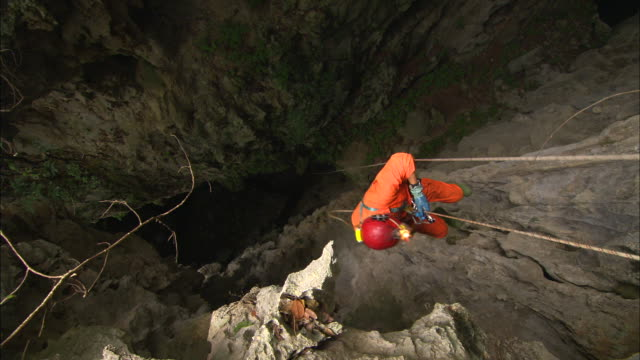 a caver abseils into a deep cavern. available in hd. - abseiling stock videos & royalty-free footage