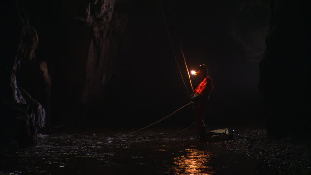 A caver detaches himself from his abseiling ropes as he stands in an underground river. Available in HD.