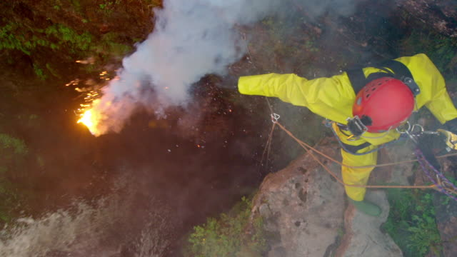 A caver, wearing high vis gear, drops a flare into Gaping Gill