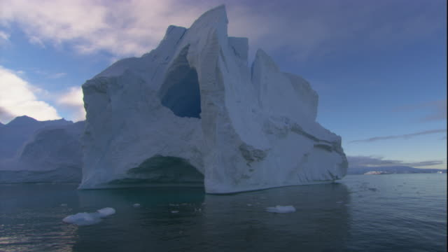 a cavernous hole in side of an iceberg on the ocean. available in hd. - antarctic ocean stock videos and b-roll footage