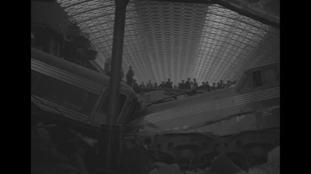 vídeos de stock e filmes b-roll de cavernous interior of union station with wreckage of passenger train / double doors with wreckage piled up against it / tilt up to higher level of... - estação de ferroviária