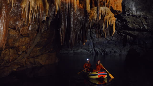 pan cavers admiring formations in a boat on underground river - using a paddle stock videos & royalty-free footage