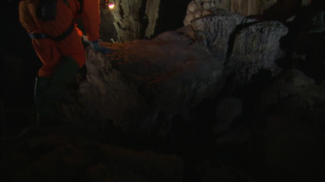 cavers climb onto the root of a giant stalagmite. available in hd. - stalagmite stock videos and b-roll footage