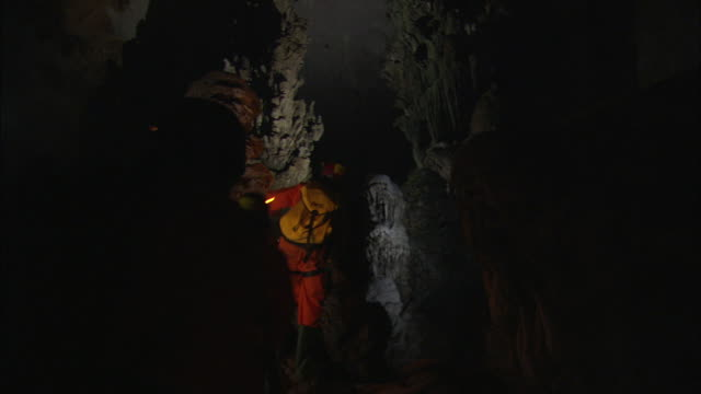 cavers climb to the root of a giant limestone stalagmite. available in hd. - stalagmite stock videos and b-roll footage
