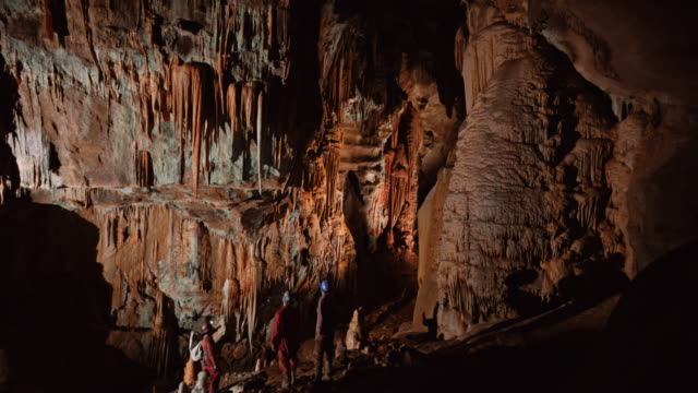 pan cavers discussing stalactites above them in the large cave - slovenia video stock e b–roll