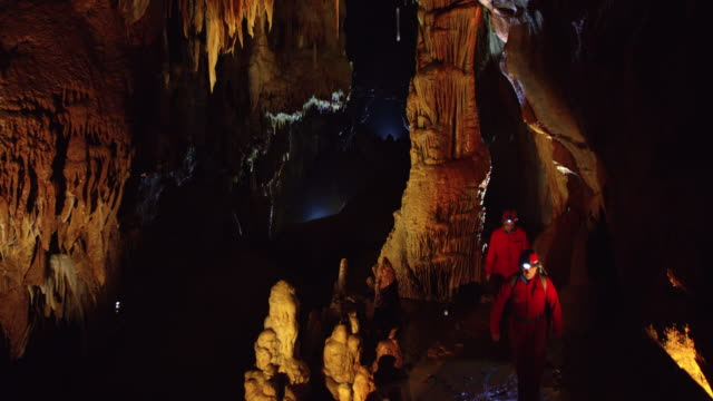 Cavers walking through beautiful cave hall